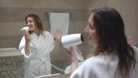 Reizend blonde Frau singt mit hairdryer Lizenzfreie Stockbilder
