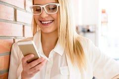 Reizend blonde weibliche Stellung im Büro mit Smartphone Stockbilder