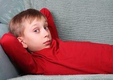 Blonder kaukasischer Junge im roten Lügen auf dem grünen Sofa, das die Kamera überrascht untersucht Lizenzfreie Stockfotos