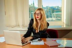 Reizend blonder Sekretär im Büro, das mit Laptop und docu arbeitet Lizenzfreies Stockbild