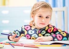 Reizend blondes kleines Mädchen zeichnet mit Bleistiften Lizenzfreies Stockbild