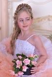 Reizend blondes Mädchen in einem weißen Kleid mit einem Pfirsich Stockbilder