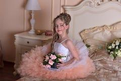 Reizend blondes Mädchen in einem weißen Kleid mit einem Pfirsich Stockfotografie