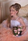 Reizend blondes Mädchen in einem weißen Kleid mit einem Pfirsich Stockfoto