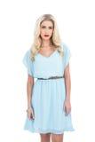 Reizend blondes Modell im blauen Kleid, das Kamera betrachtet Lizenzfreie Stockfotografie