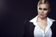 Reizend blondes Modell im weißen männlichen Hemd und in der Jacke, die beiseite mit einem Schmunzeln schaut Stockfotografie