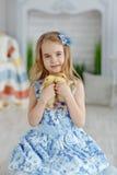 Reizend Blondine des kleinen Mädchens in einem Kleid, das Entlein, in einem L hält Stockbilder