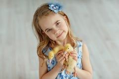 Reizend Blondine des kleinen Mädchens in einem Kleid, das Entlein, in einem L hält Stockfoto