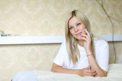 Reizend Blondine lächelt und wirft für Kamera auf, gefunden beim Schlafen Stockfoto