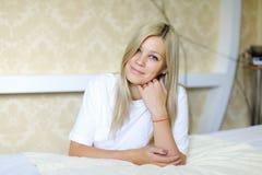 Reizend Blondine lächelt und wirft für Kamera auf, gefunden beim Schlafen Stockbild