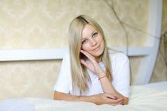 Reizend Blondine lächelt und wirft für Kamera auf, gefunden beim Schlafen Lizenzfreies Stockbild