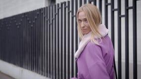 Reizend Blondine tragen modischen malvenfarbenen Mantel mit dem Pelzkragen und gehen in Stadt nahe Gebäude mit Zäunen stock video footage