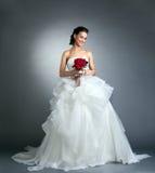 Reizend Braut mit dem Blumenstrauß, der im Studio aufwirft Stockfoto