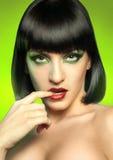 Reizend Brunette auf grünem Hintergrund lizenzfreies stockbild