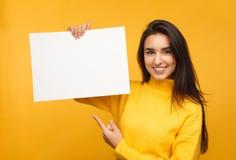Reizend Brunette, der auf leeres Papier zeigt stockbild