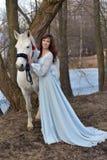 Reizend Brunette im hellblauen Kleid mit einem Schimmel Lizenzfreie Stockfotos