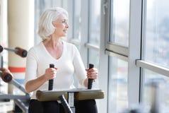Reizend dünne ältere Frau, die Turnhallenausrüstung verwendet lizenzfreies stockbild