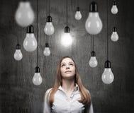 Reizend Dame betrachtet aufwärts den hängenden Glühlampen ein Konzept des Suchens von neuen Ideen Lizenzfreie Stockbilder
