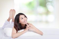Reizend Frau, die auf Bett liegt und Exemplarplatz schaut Stockfoto