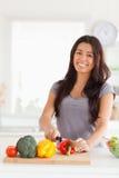 Reizend Frau, die Gemüse bei der Stellung kocht Stockbild