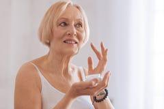 Reizend Frau, die ihre gealterte Antisorgfalt verwendet stockfotografie