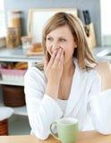 Reizend gähnende Frau beim Trinken des Kaffees Stockbilder