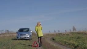 Reizend Geschäftsfrau ruft um Hilfe durch Handy Mädchen nahe defektem Auto auf Landstraße Langsame Bewegung stock video