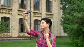 Reizend glücklicher Student mit dem kurzen schwarzen Haar, welches das selfie und Lächeln, stehend im Park nahe Universität nimmt stock footage