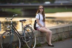 Reizend jugendlich Mädchen mit dem Fahrrad, das auf dem Damm von Fluss während des Sonnenuntergangs sitzt Lizenzfreie Stockbilder