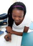 Reizend jugendlich Mädchen, welches das Lügen auf ihrem Bett studiert Lizenzfreie Stockfotografie