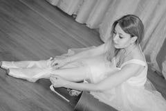 Reizend junge Ballerina setzt an Pointe-Schuhe mit Bändern stockbild