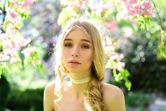 Reizend junge blonde Dame mit dem langen Kraushaar im Blumengarten Hübsches Mädchen mit Spitzestreifen auf ihrem Halsgenießen Lizenzfreie Stockbilder
