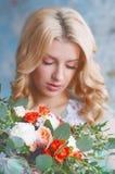 Reizend junge blonde Frau, die frische Blumen hält Lizenzfreie Stockbilder