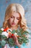 Reizend junge blonde Frau, die frische Blumen hält Lizenzfreie Stockfotografie