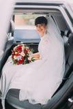 Reizend junge Braut mit ihrem Brautblumenstrauß in der Hochzeitsautolimousine Lizenzfreies Stockfoto