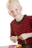 Reizend Junge, der mit Plastikkitt spielt Lizenzfreie Stockbilder