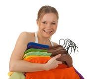 Reizend junge Frau, die bunte Kleidung anhält Stockbilder