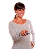 Reizend junge Frau, die eine Fernsehentfernte station verwendet Stockfoto