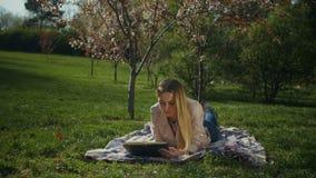 Reizend junge Frau, die im Frühjahr einen Park des Buches liest stock video footage