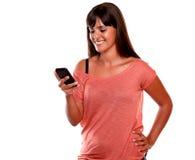 Reizend junge Frau, die Meldung durch Mobiltelefon sendet stockbild