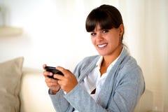 Reizend junge Frau, die Meldung durch Mobiltelefon sendet lizenzfreie stockfotografie