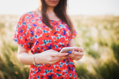Reizend junge Frau, die zum intelligenten Mobiltelefon verwendet Stockfotos