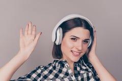 Reizend junge Frau im karierten Hemd hörend auf Musik und w stockbild