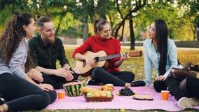 Reizend junge Frau spielt die Gitarre, die auf Decke mit Freunden auf Picknick, Mädchen sitzt und Kerle klatschen Hände stockfoto