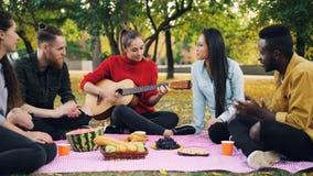 Reizend junge Frau spielt die Gitarre, die auf Decke mit Freunden auf Picknick, Mädchen sitzt und Kerle klatschen Hände lizenzfreies stockfoto