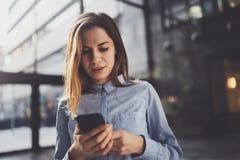 Reizend junge Geschäftsfrau, die mit Partner über Handy bei der Stellung im modernen Geschäftszentrum spricht stockfotos
