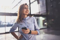 Reizend junge Geschäftsfrau, die mit Partner über Handy bei der Stellung im modernen Geschäftszentrum spricht stockbilder