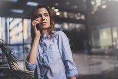 Reizend junge Geschäftsfrau, die mit Partner über Handy bei der Stellung im modernen Geschäftszentrum spricht lizenzfreies stockbild