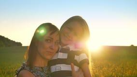 Reizend junge ihre kleine blonde Tochter umarmende, Kamera untersuchende und, Weizenfeld während des Sonnenuntergangs herein läch stock video footage