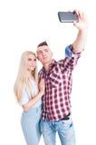 Reizend junge Paare, die ein selfie unter Verwendung des Telefons nehmen Stockbilder